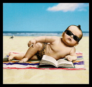 baby wearing sunglasses and side-lying on a beach with a book