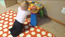baby kneeling at play table